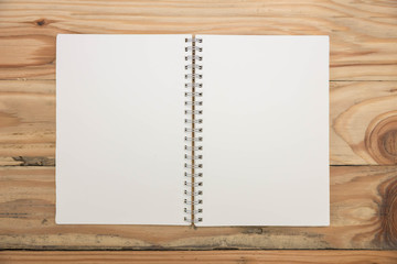 Top view of blank notebook on wooden desk.