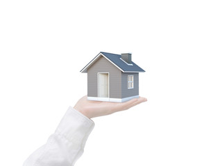 Simple house in human hand isolated on white background with clipping path. Image idea of real estate and property concept. House 3D render.