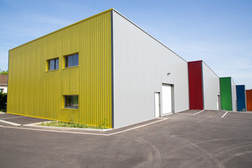 gray facade made of aluminum panels with doors and windows on industrial building