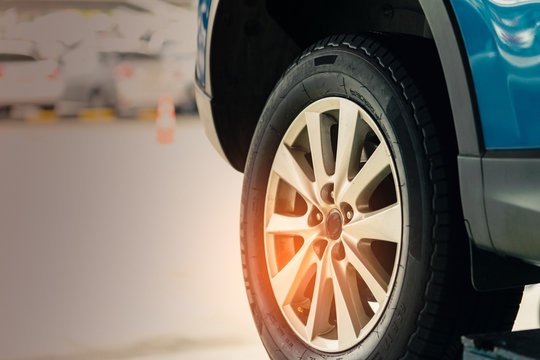 Selective focus on blue SUV car rear wheel on blurred background. Car with new high performance tire parked at garage workshop after change tyre and maintenance. Check up tire before travel concept.