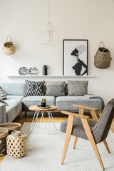 Grey armchair next to wooden table in bright interior with poster and cushions on sofa. Real photo