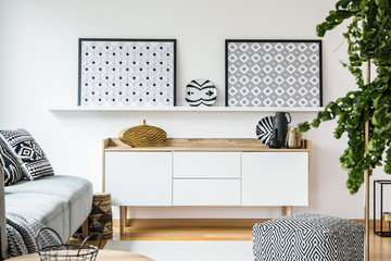 Patterned posters above cupboard in modern living room interior with settee and pouf. Real photo