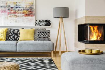Grey lamp between fireplace and couch with patterned pillows in warm flat interior with painting. Real photo