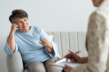 Smiling satisfied senior woman talking with psychotherapist