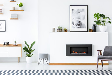 Grey armchair next to fireplace under poster in living room interior with plant and stool. Real photo