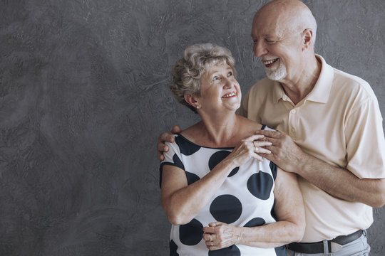 Happy and lovely senior couple against concrete wall with copy space