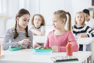 Girl talking about healthy food with friend during breakfast break at school