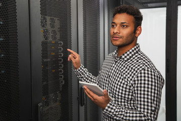 Closer look. Attractive IT guy inspecting server closet and using tablet