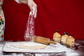 Woman cook sprinkling flour over cutting board. Cooking. Making bread on kitchen table. Cooking Process Concept