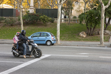 A man on a scooter with a little girl in the back seat Stopped at a traffic light