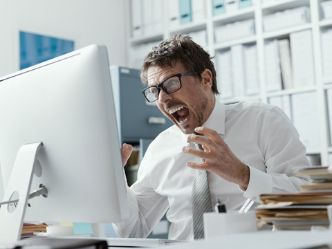 Angry business executive shouting at the computer