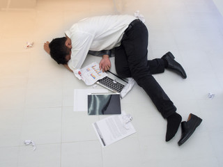 Stressed businessman lying down on the floor. There was a computer crash and the report was torn beside him.