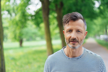 Thoughtful middle-aged man walking in a park