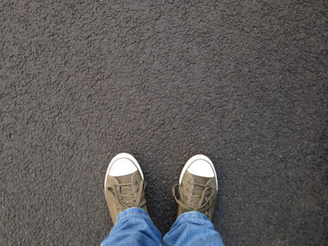 foot selfie or feet in canvas shoes standing on asphalt from personal perspective