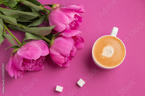 White cup with a drink of coffee with foam on a pink background two white cup with a drink of coffee with foam on a pink background two slices of sugar and pink peony flowers a concept of a summer morning and breakfast mightylinksfo