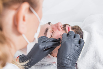 Hands using blackhead remover. How to clean pores. beautiful doctor cosmetologist in dressing gown, gloves and mask. Men's cosmetology. Portrait of handsome man getting face skin treatment