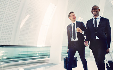 Smiling businessmen walking through an airport talking together Wall mural