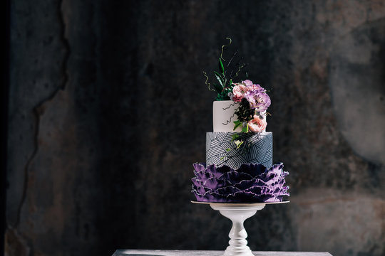 Closeup of white wedding cake with flowers on top. cake on the cake-shelf. white milk cream. cake decorated with pink and purple flowers