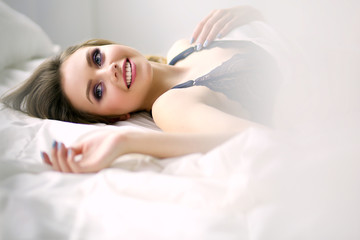 Beautiful young woman lying on white bed