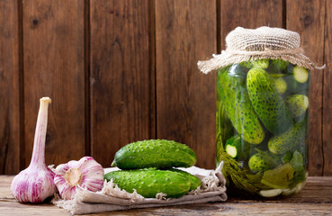 Jar of pickled cucumbers with herbs and spices