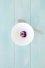 White bowl with pansy flower on mint wooden background