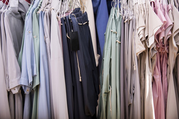Colorful nude shaped dresses  on rack with hangers. Fashion conception.