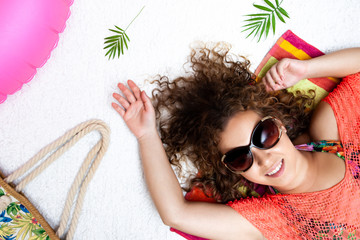 Top view vacation style portrait of a lying and relaxing beautiful woman with summer beach accessories