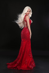 Beautiful blond woman in red dress isolated on black background. Elegant lady in long luxurious gown posing at camera.