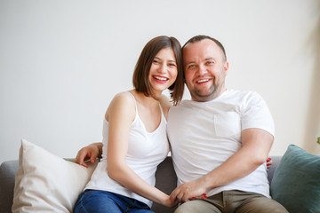 Image of young married couple sitting on sofa