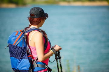 Photo from back of tourist girl with backpack and walking sticks on lake
