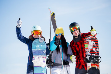Image of sports young women and men with snowboard on vacation