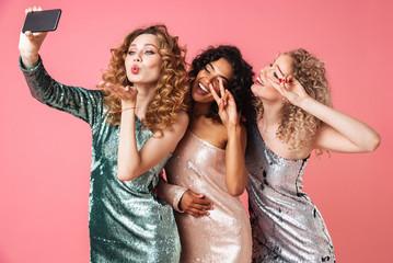 Three beautiful happy women in shiny dresses