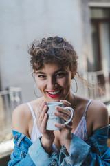 Tender girl in denim having coffee on balcony