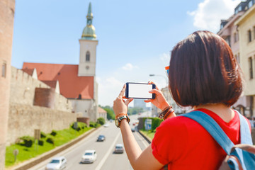 Tourist girl taking pictures on her smartphone of St Martin Church in Bratislava, Slovakia