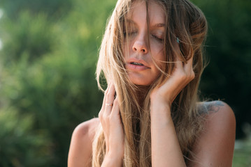Close-up of a beautiful healthy tanned face of a young girl with blond hair disheveled by the wind. The model closed her eyes and enjoyed thinking about something pleasant.