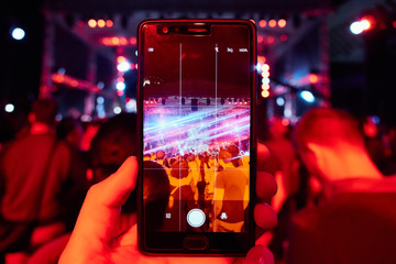 Hand with a smartphone records live music festival, live concert, happy youth