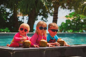 happy kids drinking coconut cocktail on beach resort