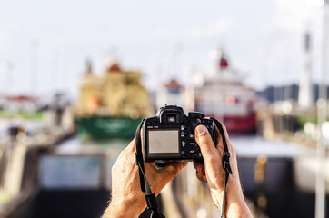Tourists shoot a photograph at the entrance of the ships in the Panama Canal. The canal cuts across the Isthmus of Panama and is a conduit for maritime trade.