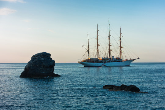 Big rock and sailing ship at sunset in front of city harbor, Skopelos island in Greece