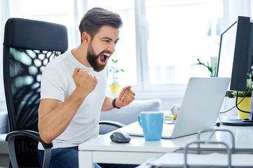 Successful man screaming excited working at home office