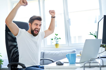 Excited successful man working in office looking on laptop