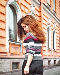A girl with long hair stands on the background of an old historic pink building in St. Petersburg