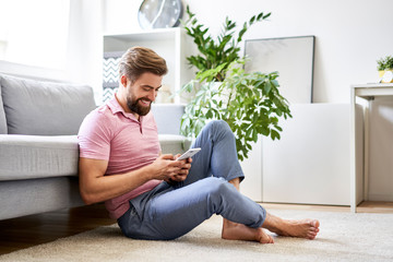 Happy, relaxed man at home using phone sitting on the floor