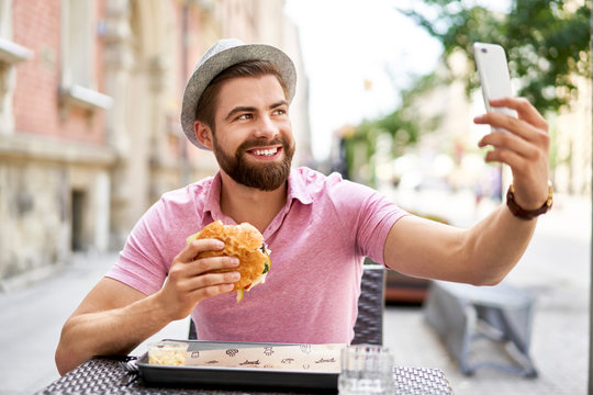 Man eating hamburger and taking selfie in the city