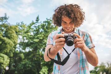 Bottom view shot of Caucasian man with curly hair checking photos in his digital camera. Young handsome male wears casual shirt, with digital photo camera standing on nature background. People, travel