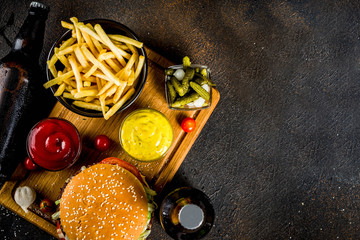 Various party food, Hamburgers, French fries, potato chips, pickled cucumbers, onions, tomatoes and cold beer bottles, rusty black concrete background copy space top view