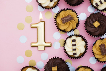 Number 1 gold candle with cupcakes against a pastel pink background