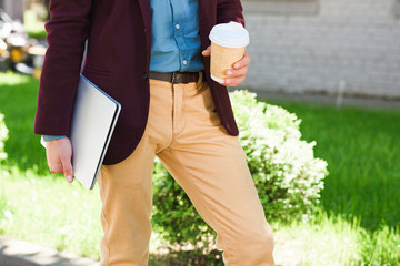 cropped shot of young man holding laptop and paper cup outside