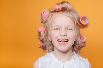 Сute little girl on morning.Happy funny child little girl with hair curlers.Portrait of preschooler girl with open mouth without milk tooth