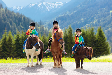 Kids riding pony. Child on horse in Alps mountains Wall mural